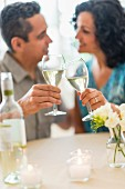 A couple celebrating in a restaurant and raising a toast with white wine