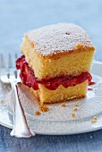 A slice of cake with strawberry jam and icing sugar
