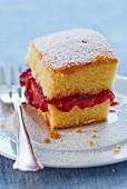 Kuchenstück mit Erdbeermarmelade und Puderzucker