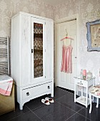 White-painted wardrobe, floral wallpaper and pink, vintage silk slip on coat hanger in bathroom