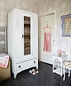 Weiss gestrichener Wäscheschrank, florale Tapete und rosa Vintage Seidenhemdchen auf einem Bügel im Badezimmer