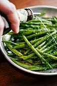 Sauce being drizzled over green beans