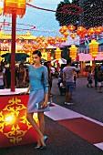 Frau im kurzen Rock und Pulli mit Tasche auf Jahrmarkt