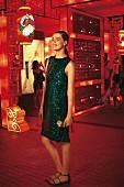 Frau im grünen Glitzer-Kleid vor roter Beleuchtung