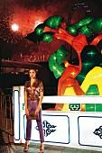 Frau in lila Seidenhose und Glitzer-Bluse mit Handtasch vor bunter Beleuchtung