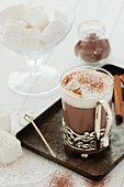 A glass cup of hot chocolate with whipped cream and homemade marshmallow cubes