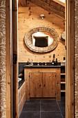 Mit ovalem Holzring gefasster Spiegel an rustikaler Holzwand und integrierter Waschtisch mit schwarzer Ablagefläche