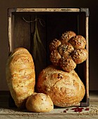 An arrangement of various types of bread in a rustic wooden box