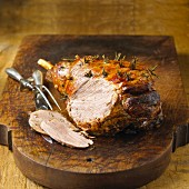 Leg of Lamb on a Cutting Board; Partially Sliced; Decanter of Wine