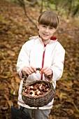 Mädchen mit einem Korb Kastanien im Wald