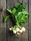 A bunch of white turnips on a wooden surface