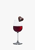 A heart-shaped praline on the rim of a glass of red wine