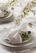 A spring wedding table set with white flowers