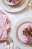 Pink cherry blossoms decorating a place setting on a wedding reception table
