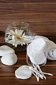 Wattepads, Wattestäbchen, Handtuch und weisse Gerbera im Wasserglas