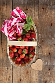 Strawberries in a wooden basket with a heart-shaped label