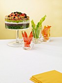 A layered vegetable dip with avocados, olives, tomatoes and yogurt