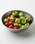 Green and red tomatoes in a stainless steel bowl