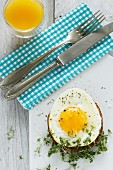 A fried egg on toast with cress and orange juice