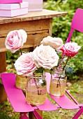 Rosafarbene Rosen in vergoldeten Gläsern auf pinkfarbenem Gartenstuhl