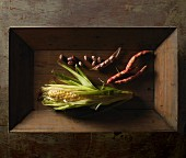 A corn cob and borlotti beans on a wooden tray