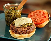 A cheeseburger with relish and tomatoes