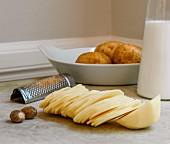 Ingredients for potato gratin: potato slices, nutmeg and milk