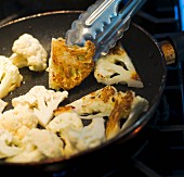 Cauliflower being fried in a pan