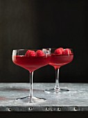 Two glasses of raspberry jelly with fresh raspberries