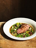 Fillet of lamb with peas, lettuce and bacon