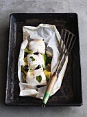 Sole fillet in parchment paper with courgettes and black olives