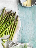 Green asparagus on a plate and butter in a saucepan