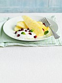 Pineapple dessert with yogurt, pomegranate seeds and mint leaves