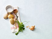 An arrangement of potatoes, herbs, onions and kitchen utensils