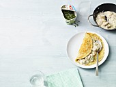 Herb pancakes with mushrooms in a creamy sauce