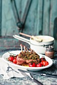 Saddle of lamb with a herb crust and oven-roasted tomatoes