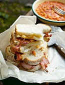 Bacon and egg sandwiches in greaseproof paper with a bowl of baked beans