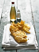 Fish and chips on newspaper with salt and vinegar