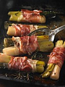 Leeks wrapped in Parma ham on a baking tray