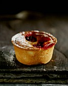 A mini cherry pie with icing sugar on a black slate