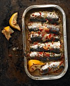 Baked sardines with chilli, garlic and lemon in an aluminium tray