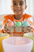 Boy dyeing Easter eggs