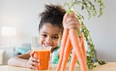 An African American girl drinking carrot juice