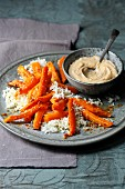 Chilli carrots on a bed of rice with satay sauce