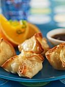 Crab rangoons with orange sauce