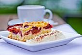 Ein Stück Pflaumen-Streusel-Kuchen mit Schlagsahne