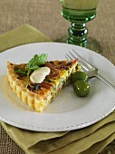 A slice of leek and bacon quiche with green olives on a plate