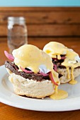 Scones topped with poached eggs, caramelised onions, beef steak and Hollandaise sauce