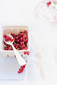 Redcurrants in a cardboard punnet with a spoon