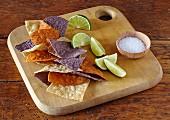Bunte Tortilla Chips, Limettenschnitze und Salz